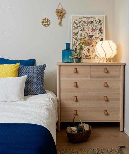 睡房設有一個淺色木抽屜櫃,睡床鋪上藍色和白色寢具。