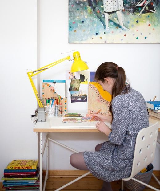Karlotta在書檯繪畫,檯上放有黃色檯燈和文件夾。