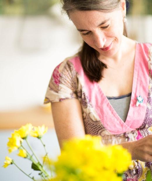 鏡頭特寫正在插黃色花的Edna。