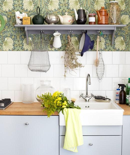 淺灰色廚櫃、木櫃台板和白色星盆,上方為瓷磚牆壁和灰色層架。