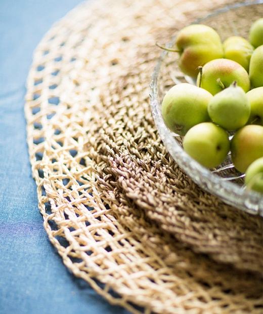 玻璃碗內放有小蘋果,底下為一疊編織餐墊。