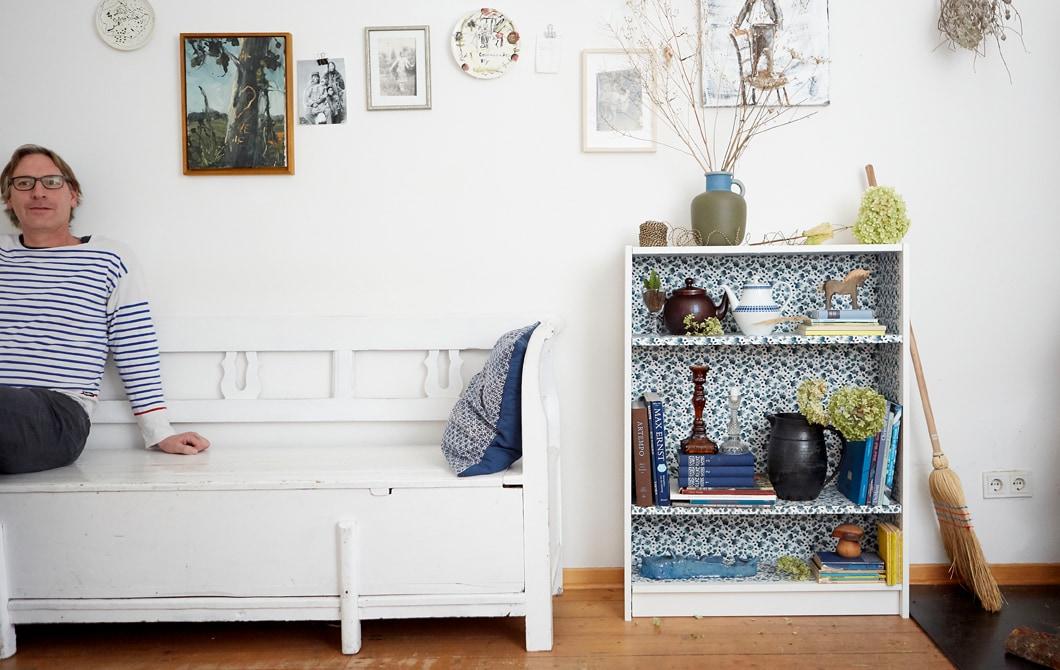 Erik坐在白色長凳上,背靠白色牆壁,旁邊的書架內飾以花卉圖案,並放有書本和擺設。