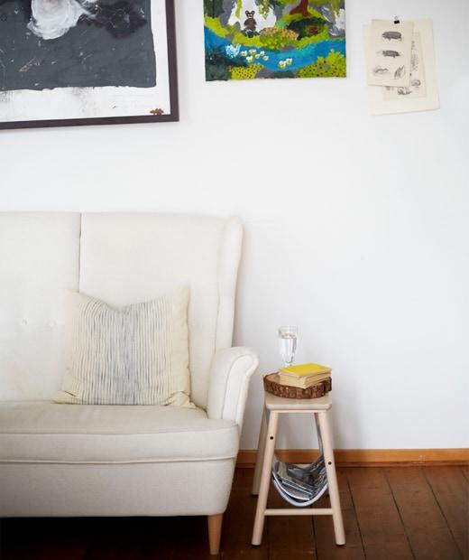 白色高背梳化和小型木製腳凳,背後的白色牆壁掛有藝術品。