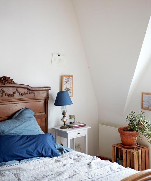 斜天花的白色睡房採用深色木床連藍色寢具,以及白色床頭几。