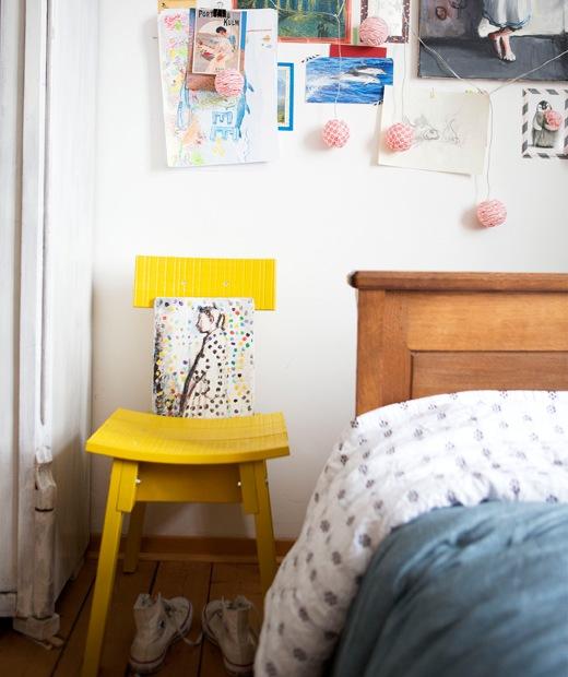 黃色椅子背靠白色牆壁,牆上飾以畫作和筆記,旁邊有一張木製睡床。