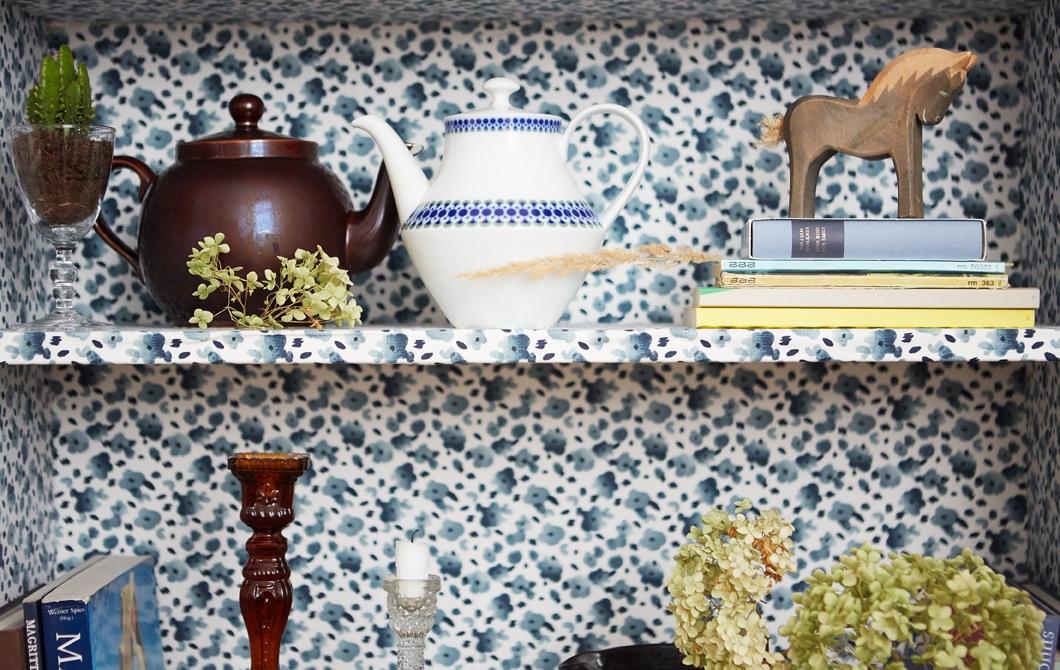 書架飾以藍色花卉圖案,架內擺放茶壺、書本和擺設。