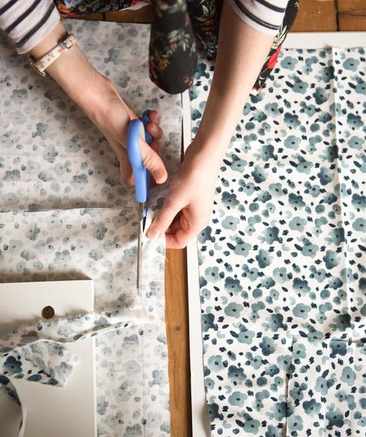 有人正在裁剪藍色花卉圖案布料。