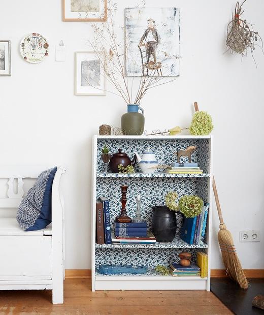 在一間白色牆壁和木地板的房間內,有一個小書架,內部貼上花卉布料,架上擺放書本和擺設。