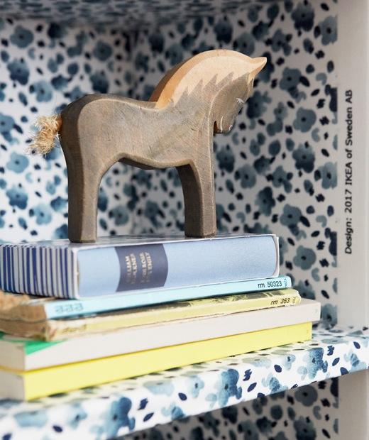 藍色花卉圖案層板的書本和小馬擺設特寫。