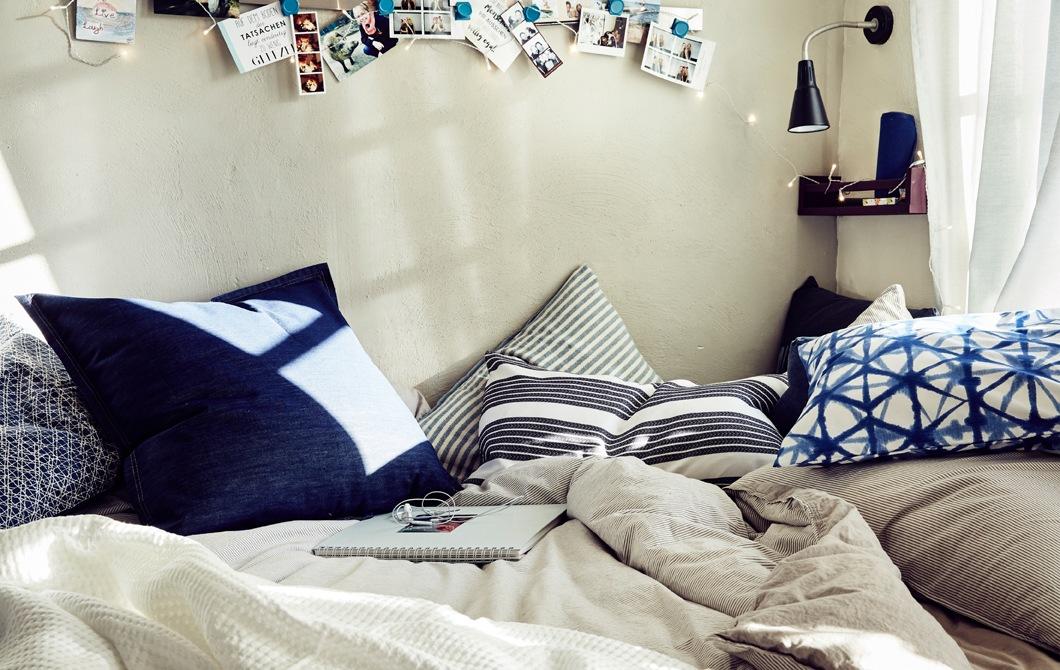 鋪上中性色調寢具和藍色圖案咕𠱸的睡床特寫。