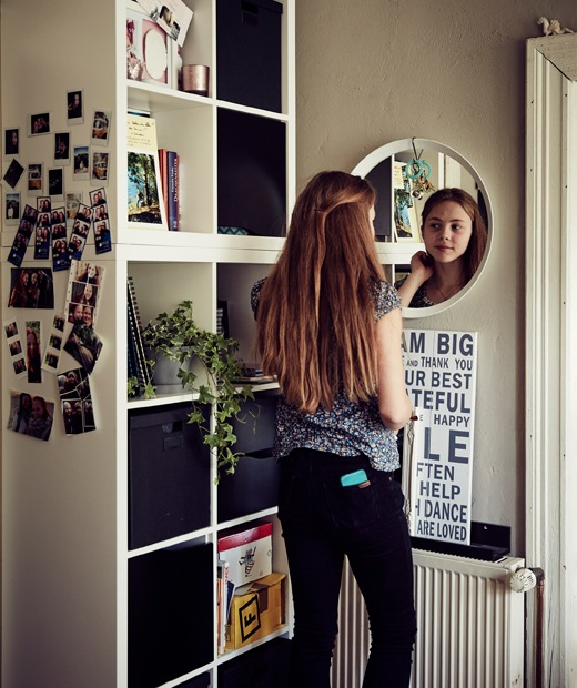 Teenager Malin looking in the mirror next to a cubed storage unit.