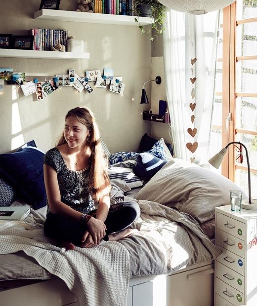 Malin坐在鋪上中性色調寢具和放有藍色咕𠱸的床上,上方裝有牆架。