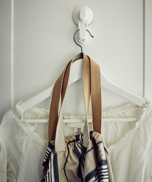 白色襯衫和袋以衣架掛在白色掛鈎上。