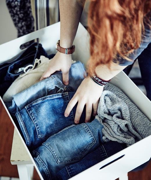 Stine正在整理摺好放在白色箱內的牛仔褲。