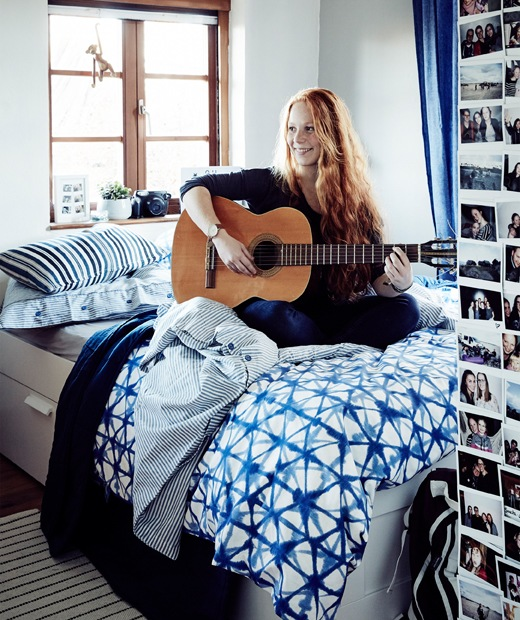 Stine在床上彈結他的照片。