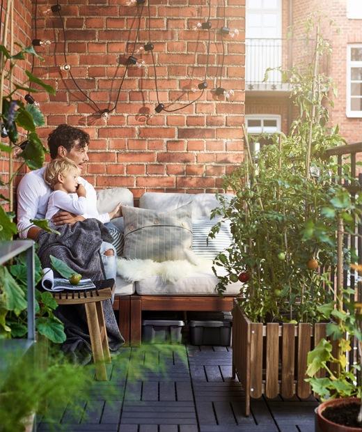 在露台上,一位男士和小孩坐在紅磚牆旁的長凳上。
