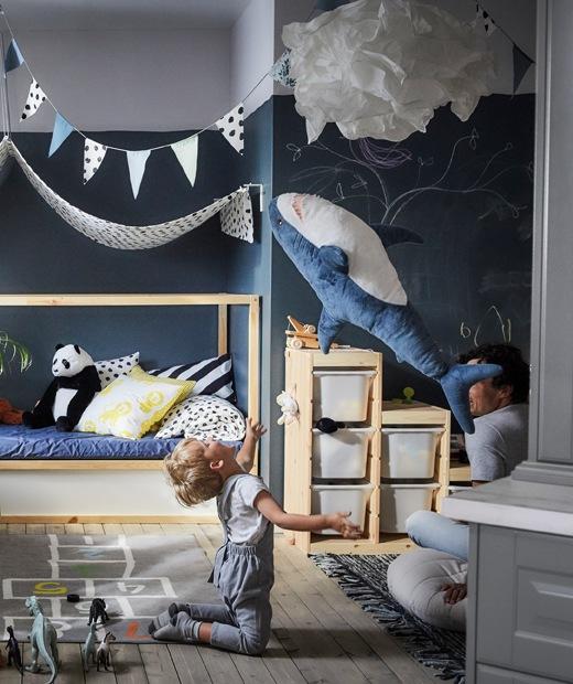 一個孩子將鯊魚毛公仔扔到半空,身後有貯物箱和布製床頂篷。