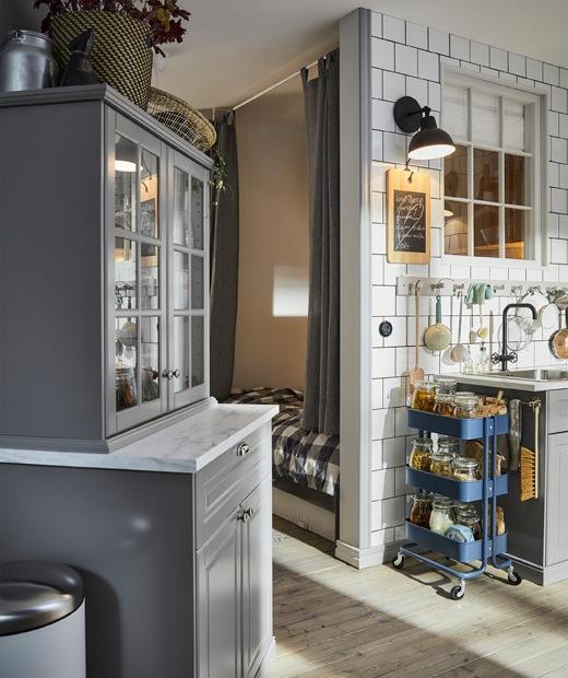 灰色廚櫃和藍色活動几,星盆上方的白色瓷磚牆上有一排掛鈎。