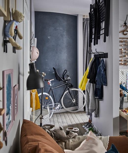 玄關牆上掛起衣物和摺椅,還有單車,以及一幅黑板牆。