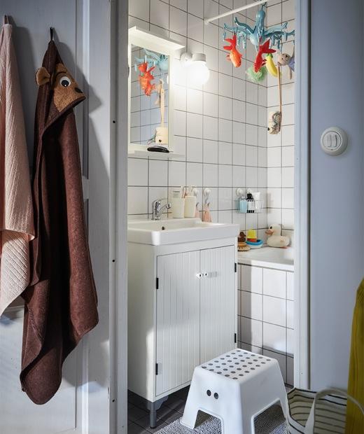 白色瓷磚小浴室,白色洗手盆櫃前放有一張腳凳。