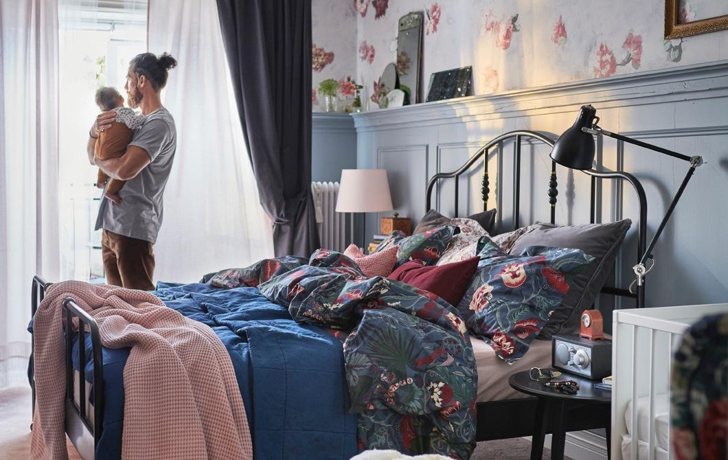 一個男人抱著嬰兒站在睡房內,房內有碎花寢具,窗邊有幾層窗簾。