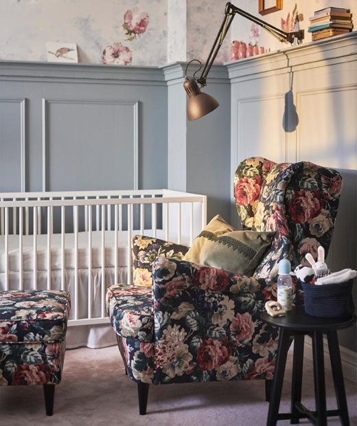 放在嬰兒床邊的碎花扶手椅及腳凳,上方有一盞夾式射燈。