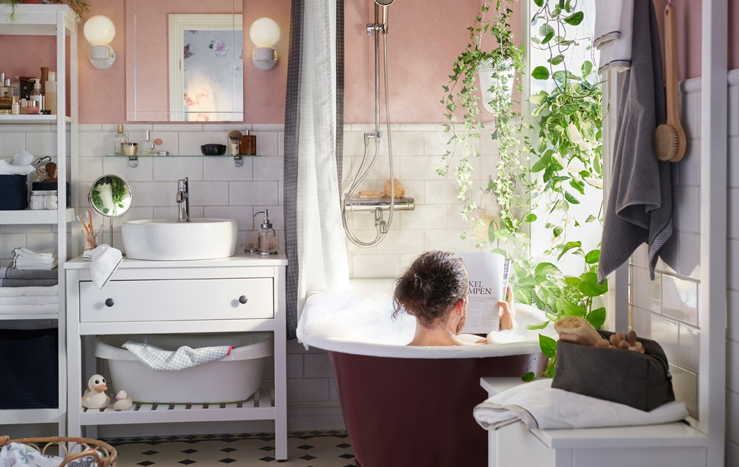 坐在浴缸內的男人,浴室設有淺粉紅色牆、白色瓷磚、白色洗手盆櫃及植物。
