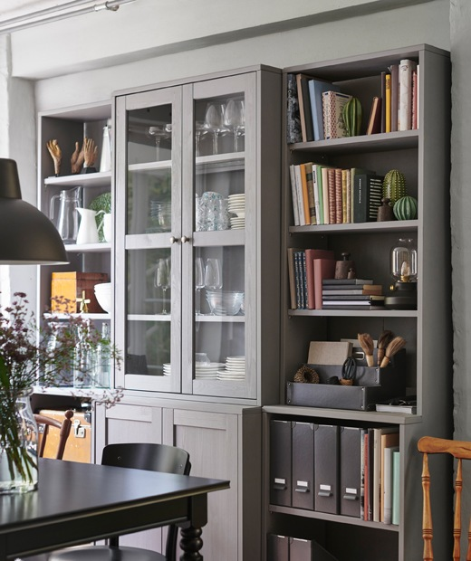 餐檯旁有一個由開放式層架及玻璃門餐具櫃組成的貯物組合,上面放有各種陶器、書本及文件。