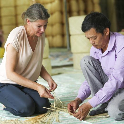 一個男人向Emma Olbers傳授傳統織竹技巧。