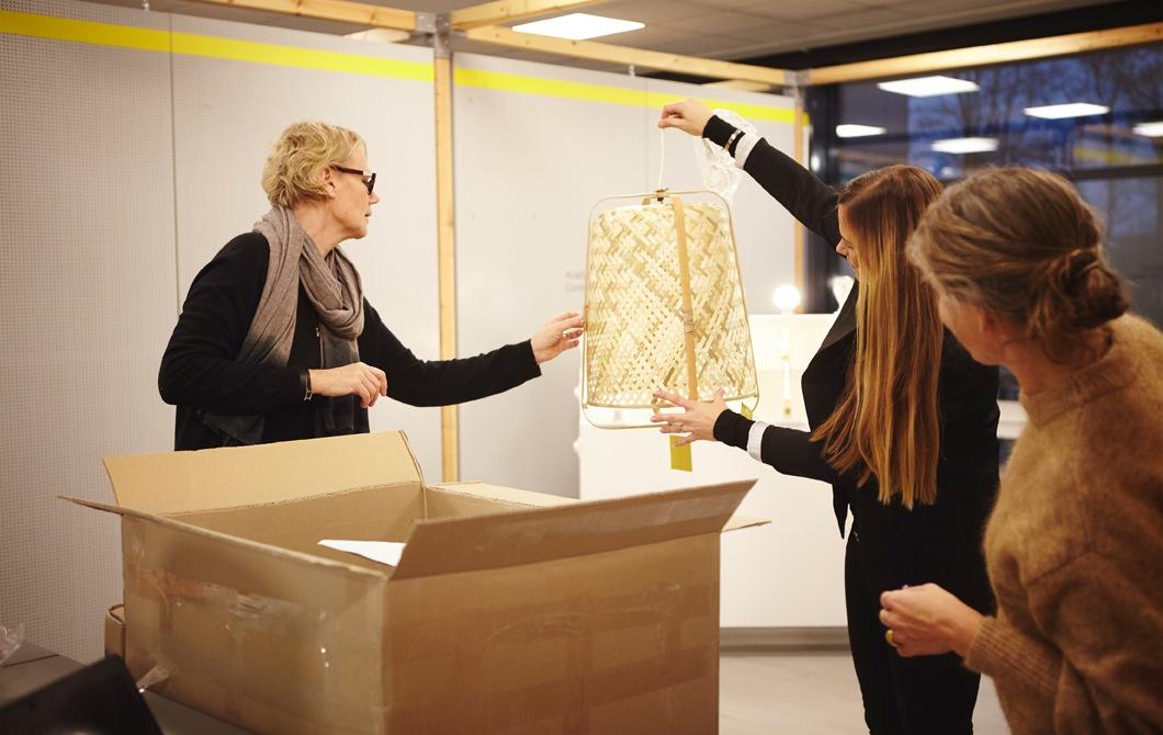 Anna Granath將竹織燈飾舉至一個大盒的上方,另外兩個人望著燈飾。