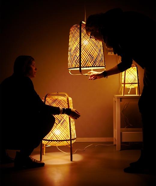 三盞亮起的竹織燈飾及兩個人影。