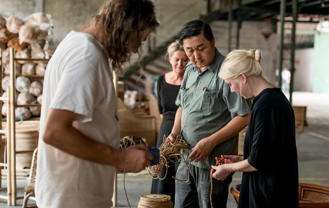 A group of people handling rope and materials in a warehouse with rattan furniture.