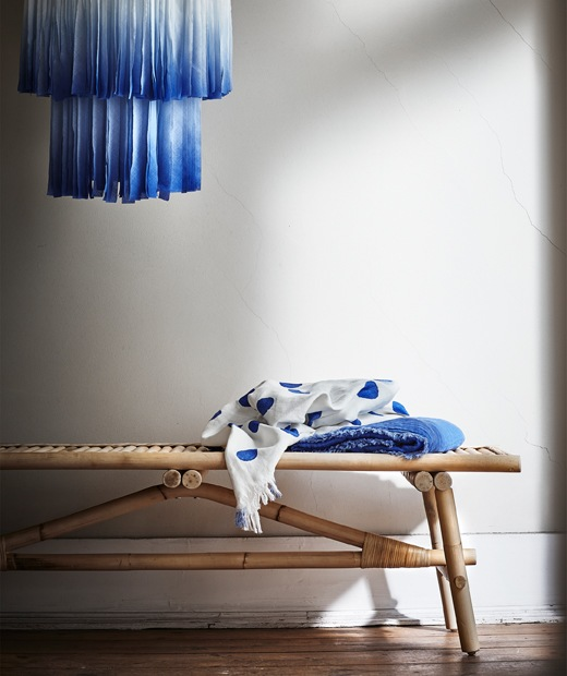 A blue fabric lampshade hanging above a rattan bench.