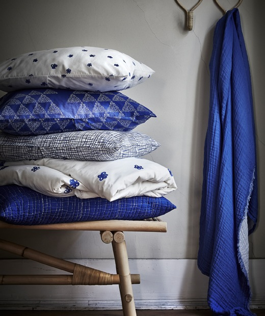 Blue and white patterned cushions piled up on a rattan bench and blue fabric hanging from a hook.