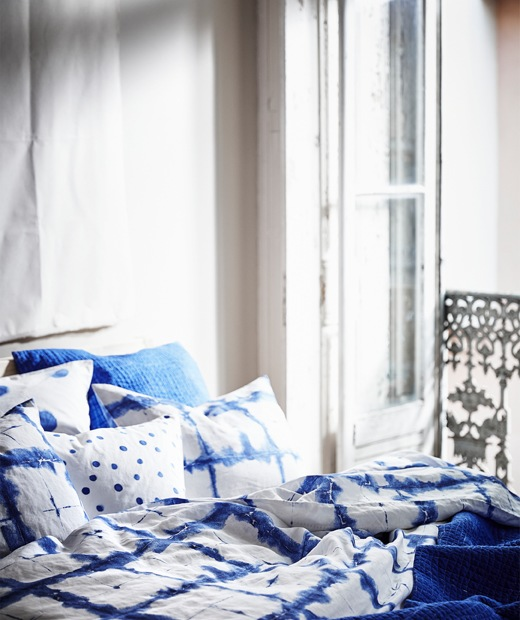 Blue patterned bedding layered on a bed next to a balcony door.