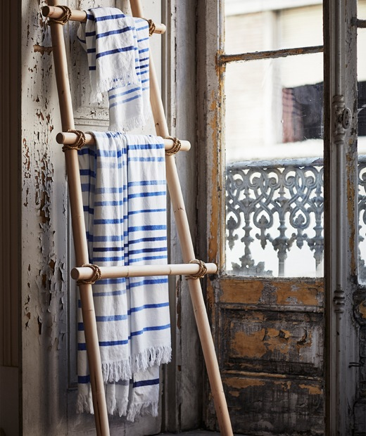 Blue and white striped fabric hanging on a wooden ladder shelf leaning against a wall.