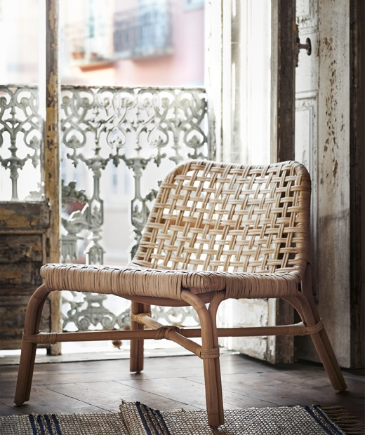 A rattan chair standing in the doorway of a rustic balcony.
