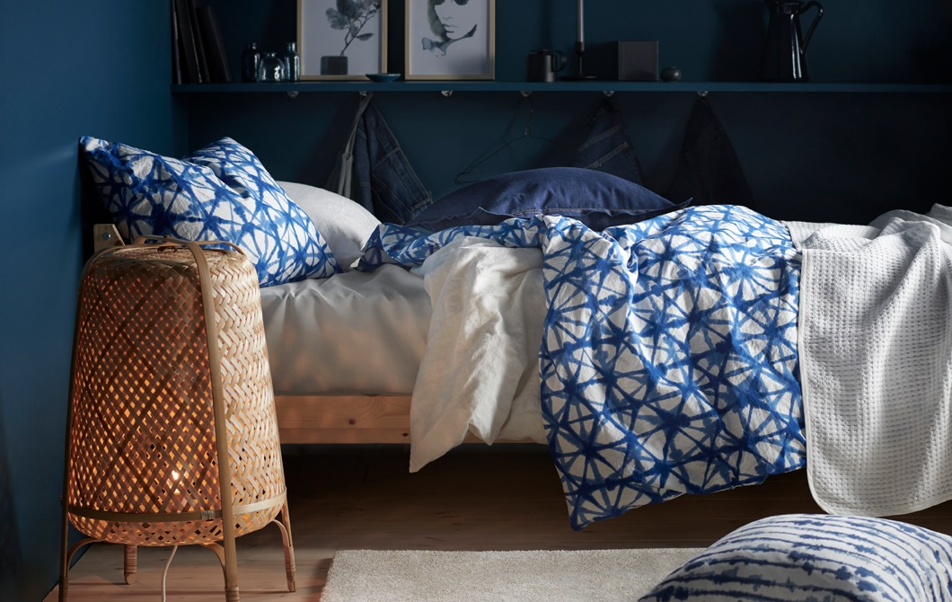 在深藍色牆壁的房間內,床上擺放藍白色圖案床上用品,還有一盞竹製座地燈。
