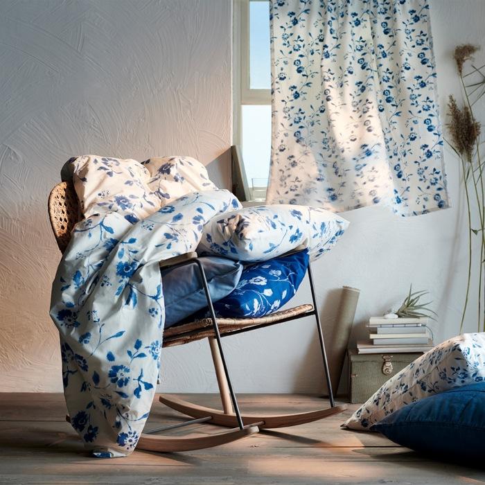 放在織藤搖椅上的藍白色碎花布藝產品,後面的窗戶掛著碎花窗簾。