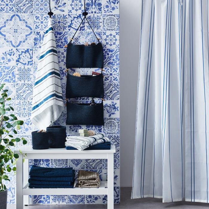 鋪設藍白色瓷磚的浴室,內有條紋浴簾、懸掛式貯物袋,以及疊放在貯物櫃的毛巾。