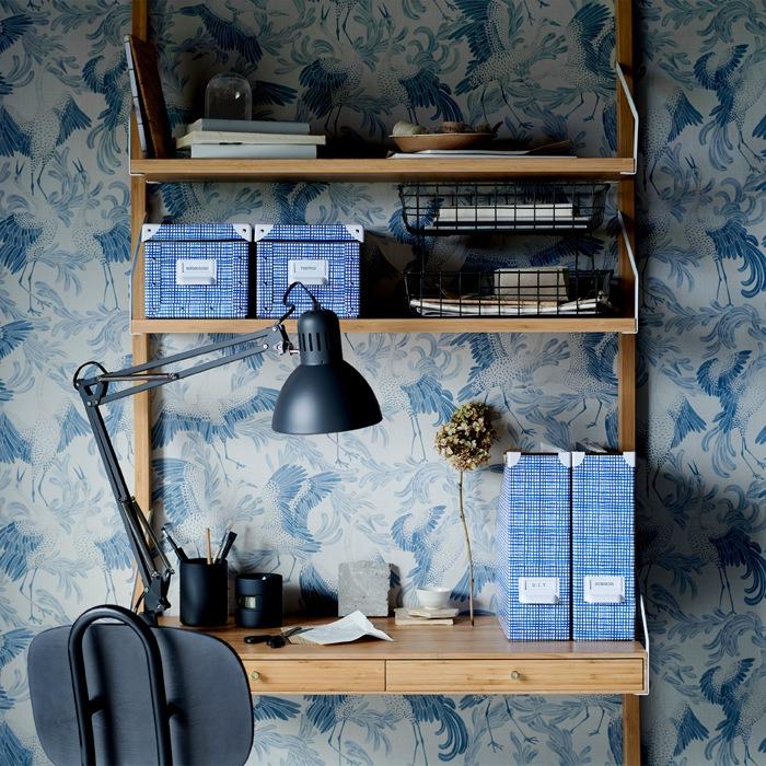 木製書檯連層架上有藍色圖案貯物盒及雜誌座,以及黑色工作燈。