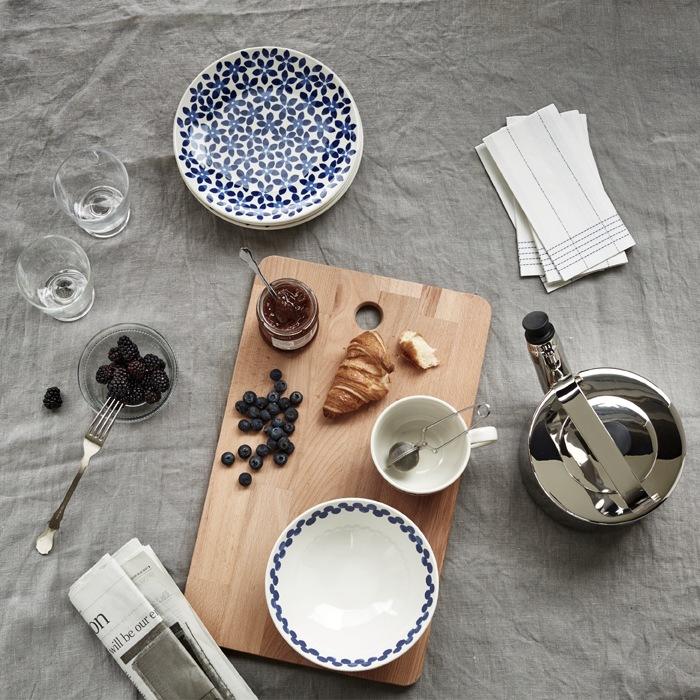 放在木砧板上的牛角包、果醬及漿果,旁邊有幾隻圖案碗碟、茶壺及報紙。