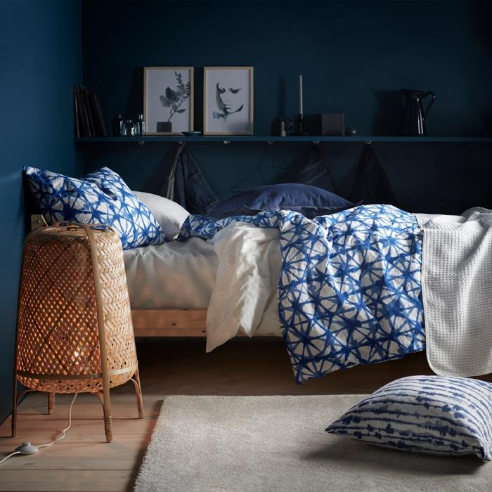 在深藍色牆的房間內,床上擺放藍白色圖案床上用品,還有一盞竹製座地燈。