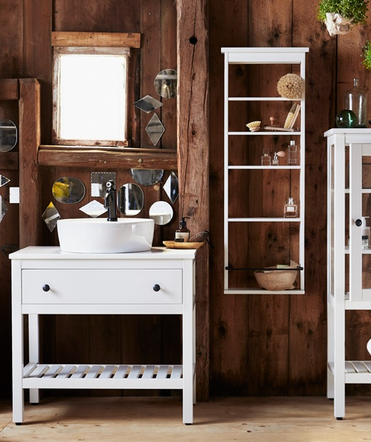 A bathroom with dark wooden walls, a white vanity unit with drawer, and white shelves on the wall.