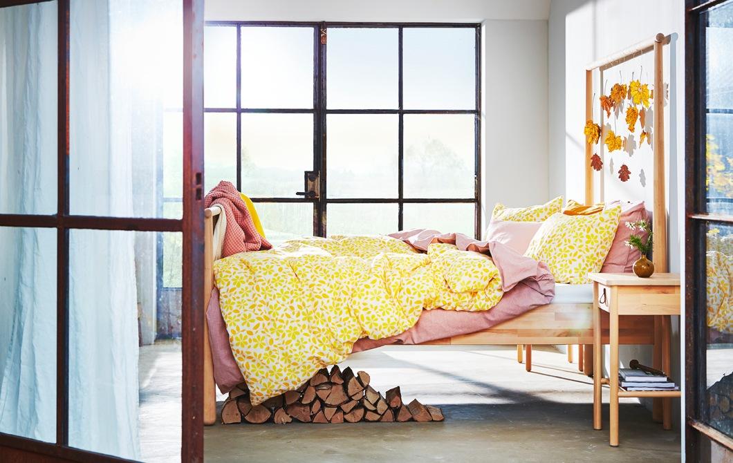 設有大窗戶的睡房,木床架上吊著一些樹葉,床上有黃色及粉紅色的床上用品。