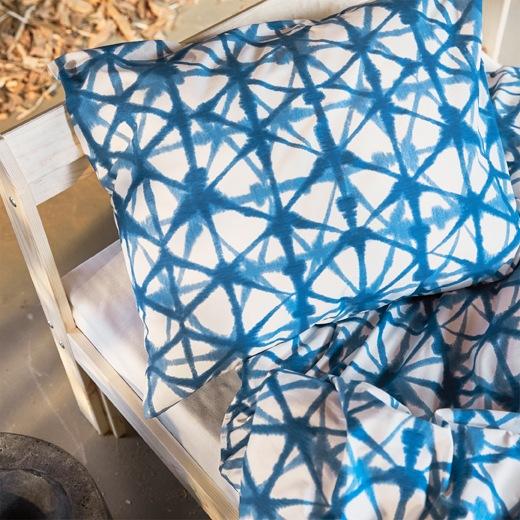 木製床架上的STJÄRNFLOCKA藍色圖案床上用品特寫。
