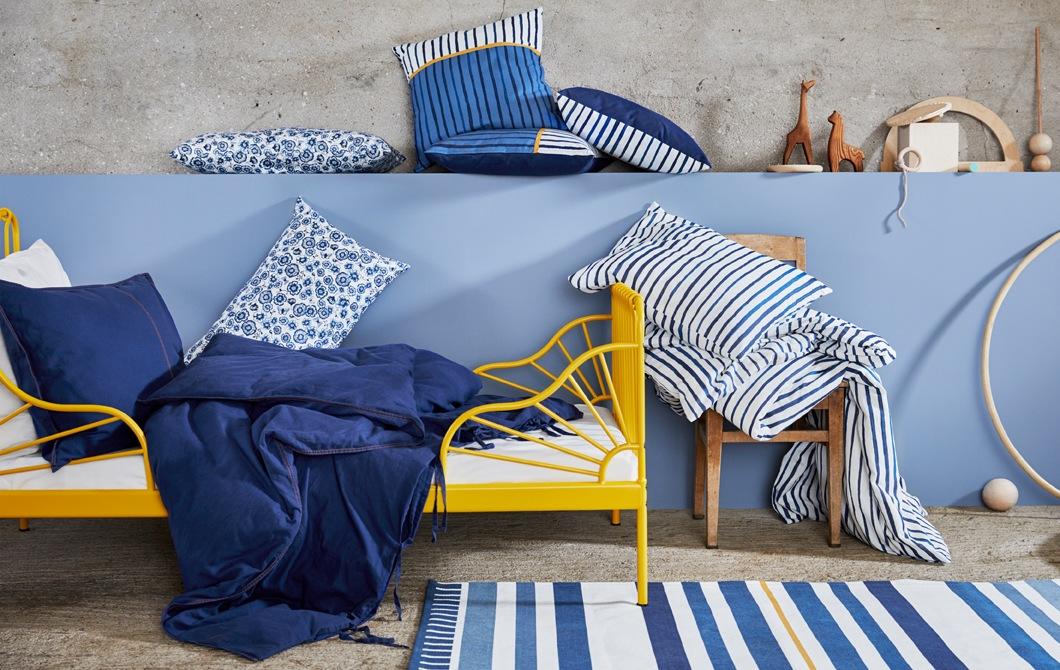 黃色床架、藍白色碎花及條紋床上用品、咕及木製玩具,背面是一道藍色牆。