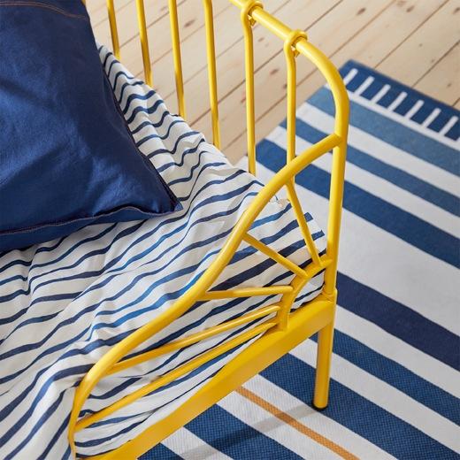 黃色床架、藍白色條紋床上用品及地氈一角特寫。