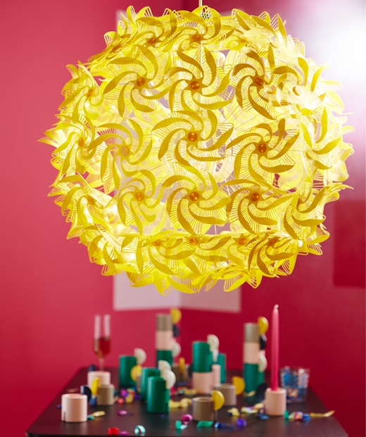 A big, yellow pendant lamp made from origami-inspired spirals connected to a round shape emits diffused light in a red room.