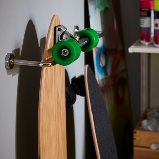 A skateboard hanging from a chrome effect IKEA VOXNAN towel rail attached to a wall.